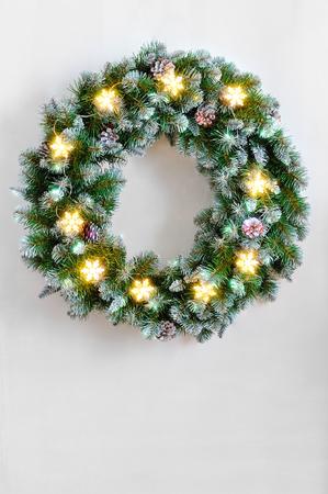 coronas de navidad: Corona de Navidad con guirnalda encendida de copos de nieve en la pared blanca