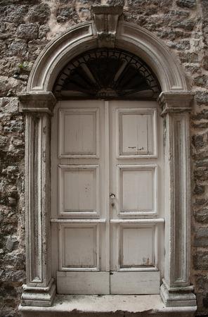old doors: wooden old door with stone door aperture into stone ancient buiding Stock Photo