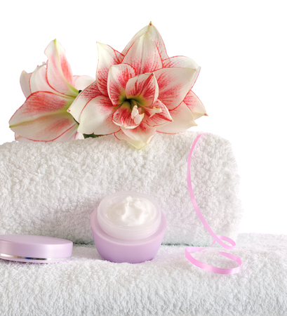 white towel: stacked white towels with pink flowers and cream isolated on white background