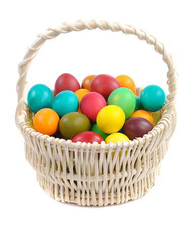 eastertime: colorful easter eggs in basket isolated on white background