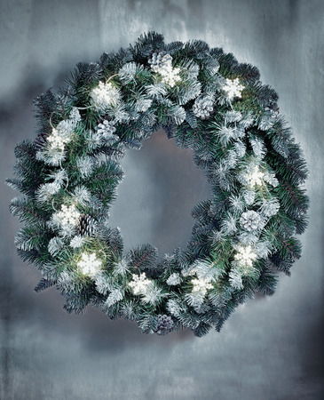evergreen wreaths: Christmas wreath with lighted garland of snowflakes on  wall