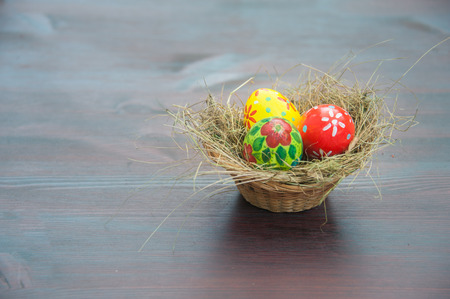 basket with painted eggs  and red lilly flower on table in garden