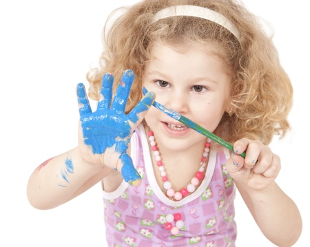 brush in: Beautiful baby covered in bright paint with paint brush Stock Photo