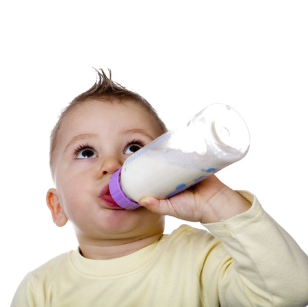 Baby is drinking milk from a baby bottle by herself photo