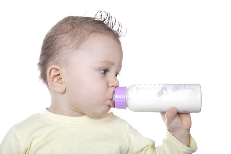sucking milk: Baby is drinking milk from a baby bottle by herself