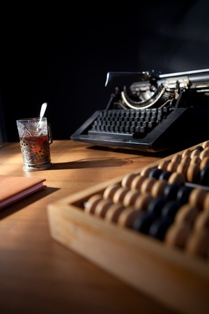a writers desk with an old typewriter a notebook and pen and a cup of tea. photo