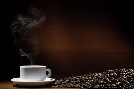 steaming coffee: Hot coffee in a cup and grains on brown Stock Photo
