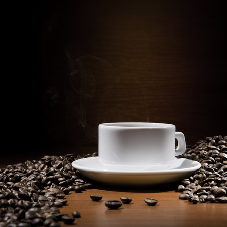 steaming: Hot coffee in a cup and grains on brown Stock Photo