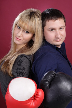 attractive family couple in  boxing gloves on red photo