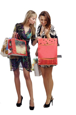two stunning girls looking in shopping bads photo