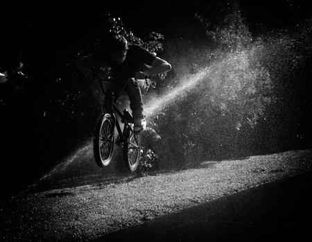 boy jumping through fountain on bmx photo