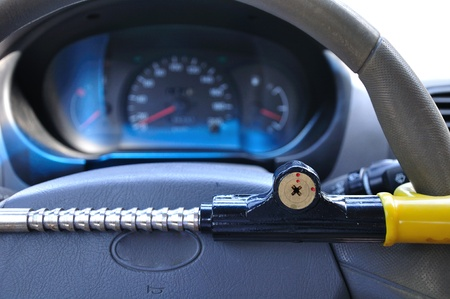 car wheels: Car antitheft mechanical device which locks the steering wheel.  Stock Photo