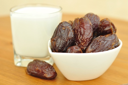 Dates and a glass of milk on a wooden table. Imagens