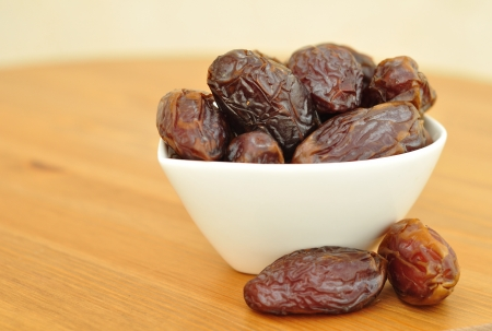 Dates in a white bowl on wooden table.