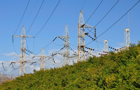 Group of electric pylons on a hill under blue sky Stock Photo - 13228804