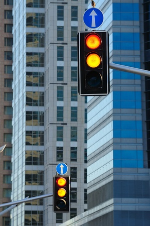 Two traffic lights against urban background of modern buildings  Stock Photo