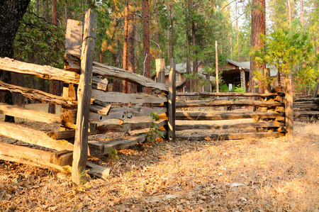 Wooden fence around house in forest of California.