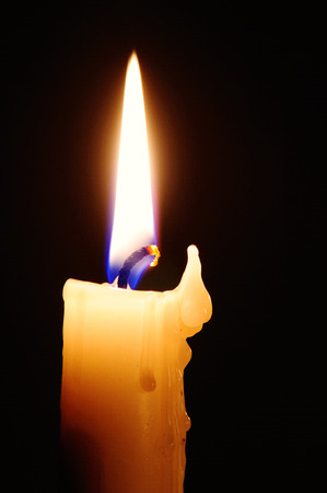 witchery: Candle with melted wax against dark background.