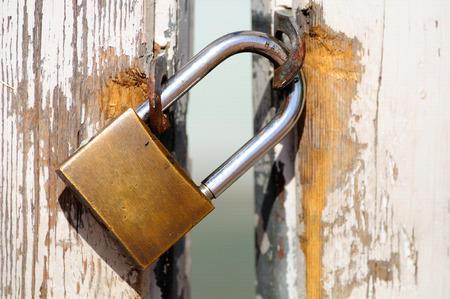 Old wooden gate locked with padlock. Stock Photo