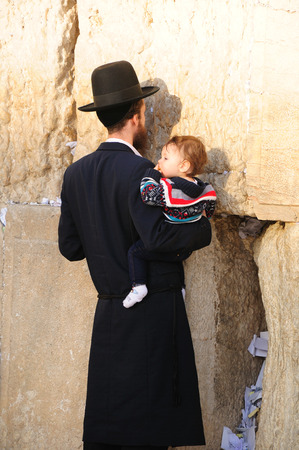 hasid: Religious orthodox jew with his child praying at the Western wall in Jerusalem old city.