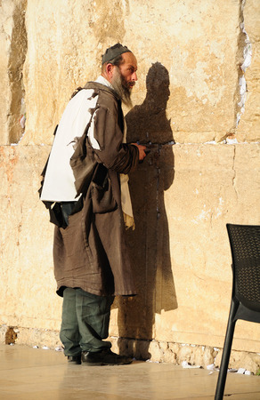hasidic: Poor religious jew in torn clothes praying at the Western wall in Jerusalem old city.