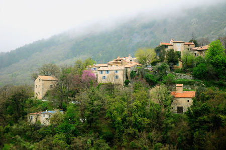 Remote French village on the hill under foggy weather. Stock Photo