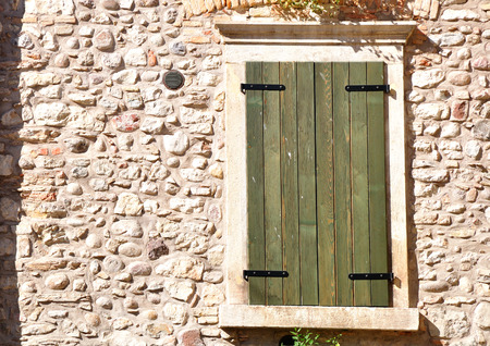 Window of Italian house shuttered with wooden shutters. Stock Photo
