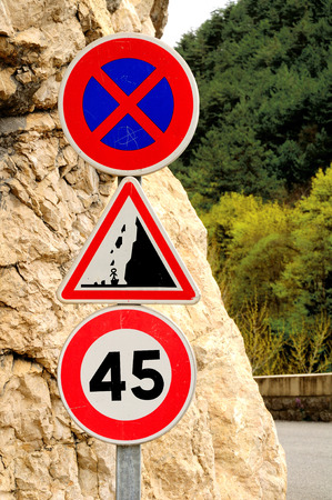 stopping: Three  traffic signs: speed limit sign, no stopping sign and the sign warning about rockfall. France.