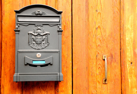 dropbox: Retro styled post box on wooden door. Verona. Italy.
