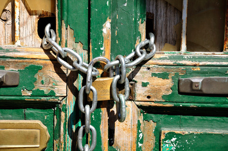 Old wooden door locked with padlock and chain.