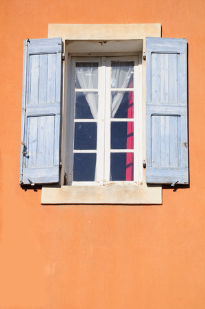Old styled window with open wooden shutters. France.