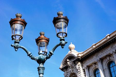 Ornate street light under blue sky in Monaco. Imagens