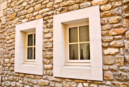 Ramshackle stone wall of medieval french house with the modern windows. Stock Photo