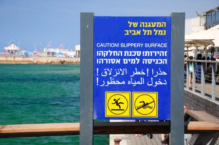 Warning signboard in Tel Aviv old port. Written in three languages. Imagens