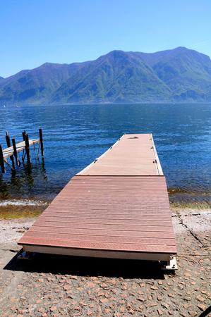 Wooden pier at the shore of Lugano lake. Switzerland.
