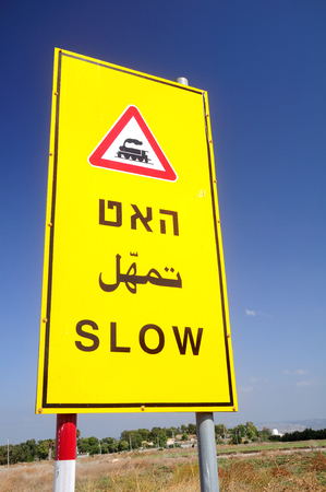 Israeli railroad crossing sign written in three languages - Hebrew, English and Arabic.