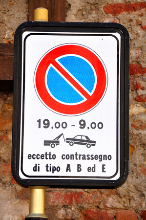Italian traffic sign showing prohibited parking hours and evacuation warning.