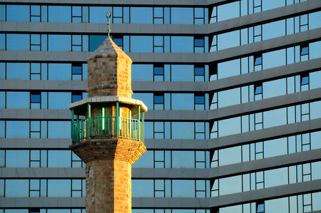 holyland: The minaret of tel aviv mosque against modern hotel. Stock Photo