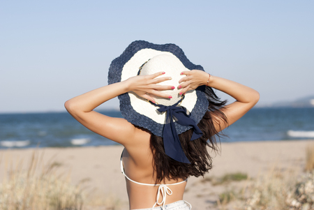 Young woman in hat standing on beach