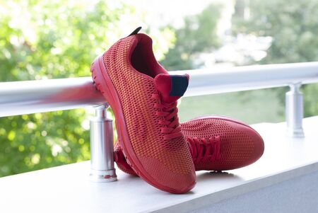 Red womens sneakers pair on green background 写真素材
