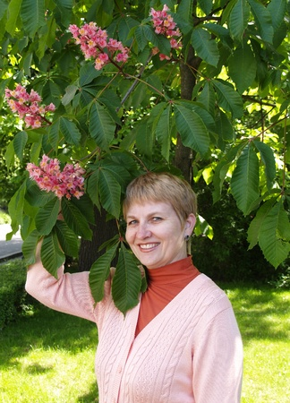 The woman looks at a horse-chestnut inflorescence photo