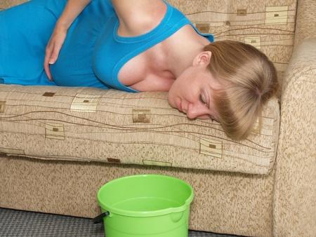 vomito: Toxicosis. La mujer embarazada se encuentra en un sof� Foto de archivo