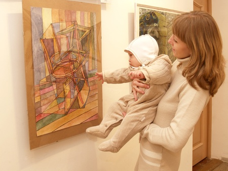 Young mother shows to the baby a picture at an exhibition photo