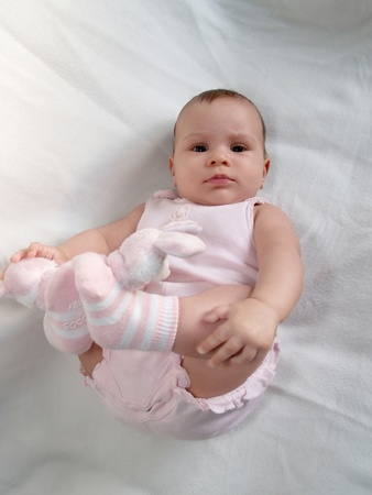 The baby holds hands feet, lying on a back photo