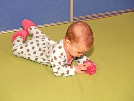 considers: The little girl considers a prorezyvatel, lying on a stomach Stock Photo