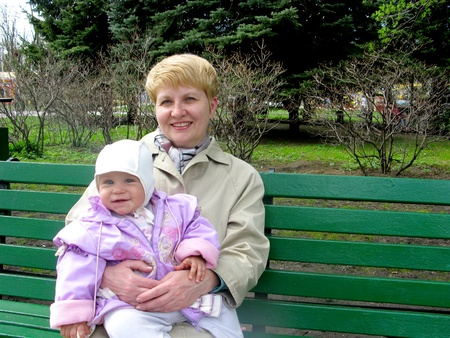 The grandmother with the granddaughter sit on a bench in park Stock Photo