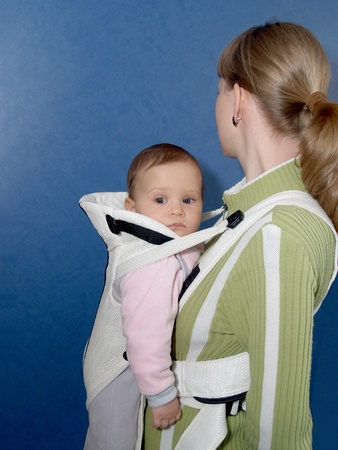 2 5 months: The woman keeps the child in a baby sling, a side view