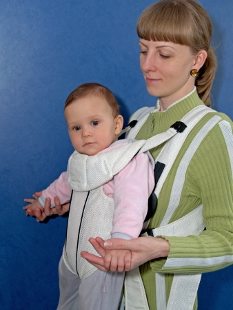 The woman keeps the baby in a baby sling photo