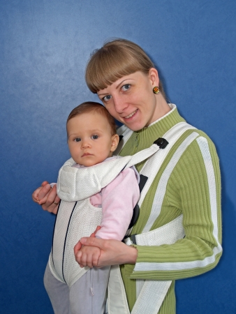 age 25 30 years: The woman keeps the baby in a baby sling Stock Photo