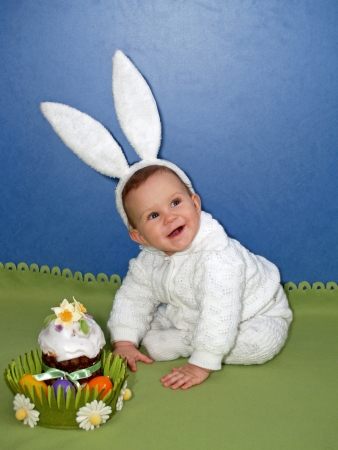 The baby in a suit of the hare with an easter Easter cake photo